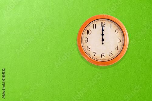Leinwanddruck Bild Clock showing 12 o'clock pm on a green wall