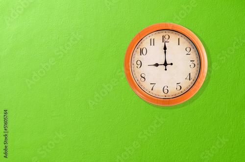 Leinwanddruck Bild Clock showing 9 o'clock on a green wall