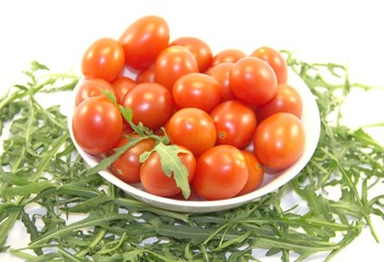 Fresh cherry tomatoes in a plate and rocket isolated on white