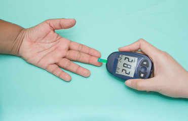 Diabetic patient measuring glucose with glucometer