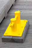 Closeup of Bright Yellow Boat Cleat on a dock pier
