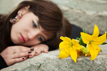 Young woman with a flowers lying on the tombstone