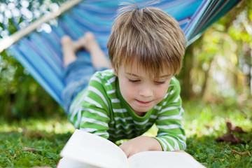 kleiner junge liest im garten
