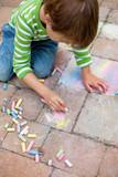 kleiner junge malt mit kreide