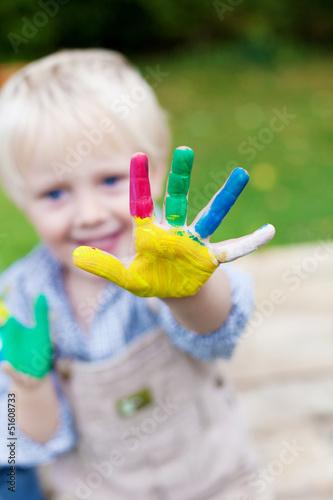 süßer junge zeigt seine bunten finger