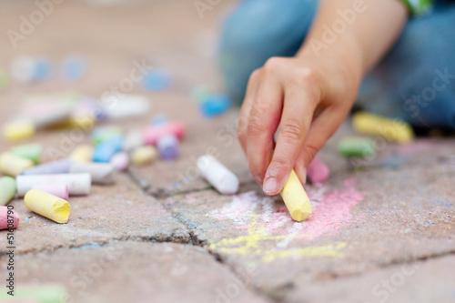 kleiner junge malt mit straßenkreide