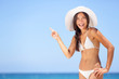 Beach woman pointing showing vacation concept