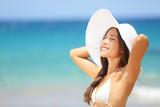 Relaxing beach woman enjoying the summer sun happy