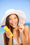 Sunscreen woman applying suntan lotion laughing