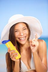 Sunscreen woman applying suntan lotion laughing
