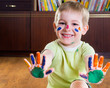 Smiling little boy showing his hands in paints