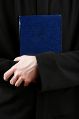 Priest holding holy bible, close up