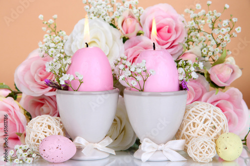 Easter candles with flowers on beige background - 51611786
