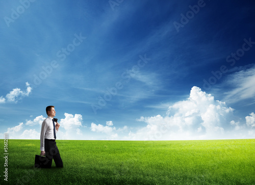 young business man wolking at the field of grass