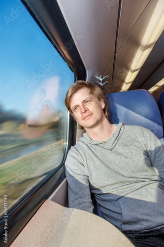 Man traveling by train, looking at the window