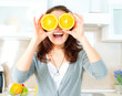 Funny Woman with Orange over Eyes in the Kitchen