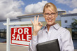 Businesswoman In Front of Office Building and For Sale Sign