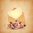 Three roses in front of an old envelope with a letter. Love lett