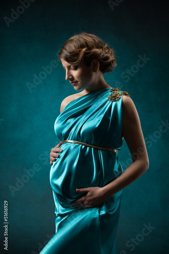 Pregnant woman in blue silk dress, beautiful pregnancy.