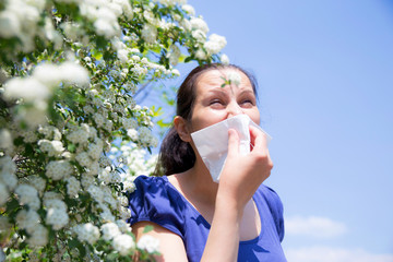 Allergic woman sneezing in handkerchief