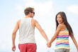 Happy cheerful young trendy couple holding hands