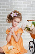 Girl in orange dress with vintage pram
