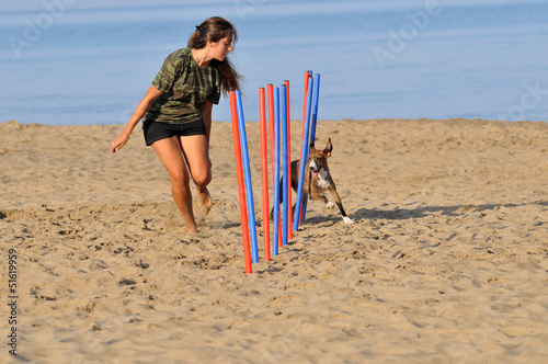 Agility dog : girl trains his  dog on the beach