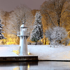 snow on trees in Riga park and lighthouse