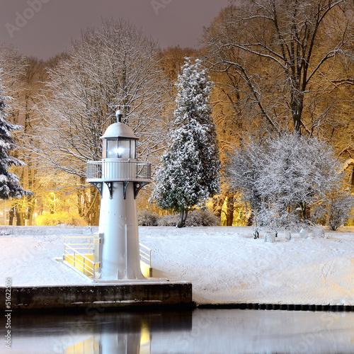 śnieg na drzewach w parku i latarnia morska w Rydze