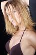 Blonde sexy Frau mit Haaren im Gesicht blickt