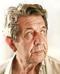 Elderly closeup sad man's face over white background
