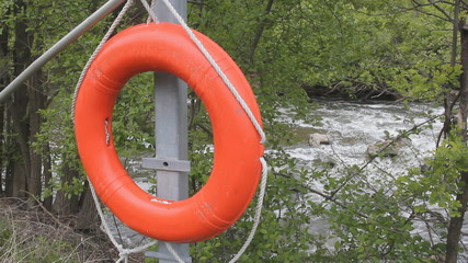 Lifesaver. Orange lifering with rushing river in background.