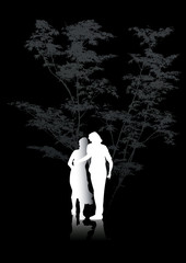 man and woman walking in the forest