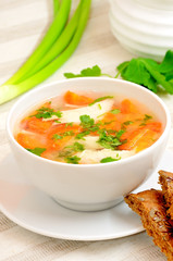 Chicken soup with vegetables in white bowl