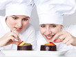 Two female chef bakers in uniform tasting a dessert