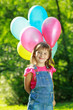 Little happy girl holding colorful balloons in green park