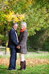 glückliches älteres paar spaziert durch den wald