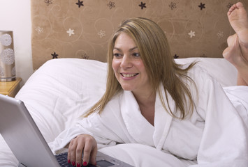 Woman laid on bed using Laptop