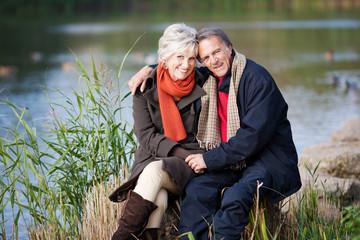 glückliches älteres paar sitzt am see
