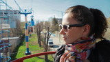 girl in sunglasses rides through the city on the cable car