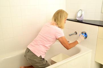 Frau putzt Armaturen in der Badewanne