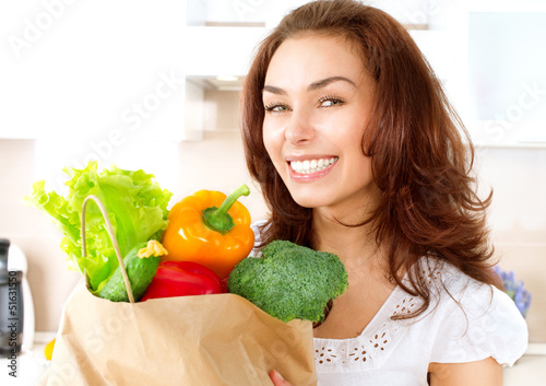 Happy Young Woman with vegetables in shopping bag