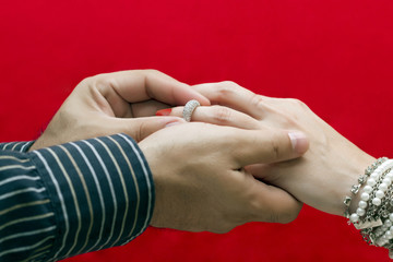 Hombre coloca anillo de compromiso a su pareja