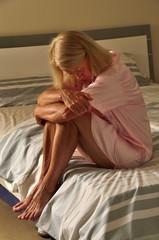Seniorin sitzt auf Bett mit Depressionen