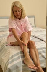 Seniorin sitzt auf einem Bett und massiert ihre Beine