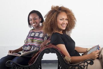Dos bellas mujeres sonríen mientras leen sentadas