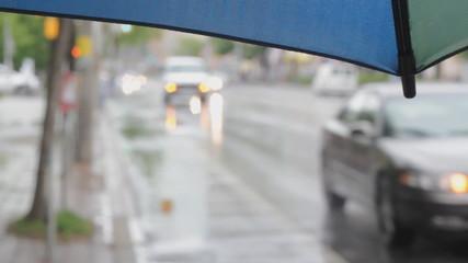 Umbrella with rainy defocused street. Toronto, Ontario.