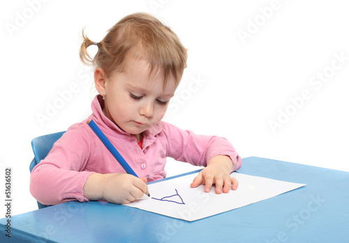 Little scholar writing in the school desk.