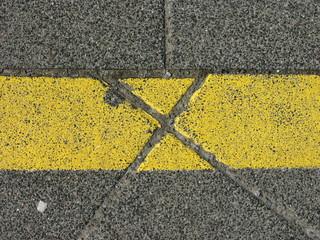 Gelbe Markierung auf dem Gehweg an einer Bushaltestelle