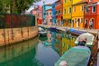 Burano street with colorful houses and people walking around